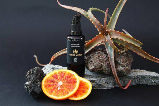 nerolipom moisturiser next to a slice of orange