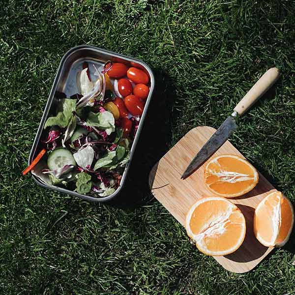 sustainable reusable salad sandwich box with bamboo lid black and blum outdoors with oranges