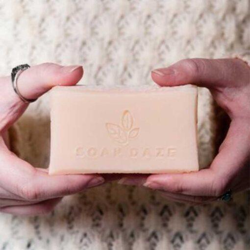 woman holding plastic free soap bar by soap daze