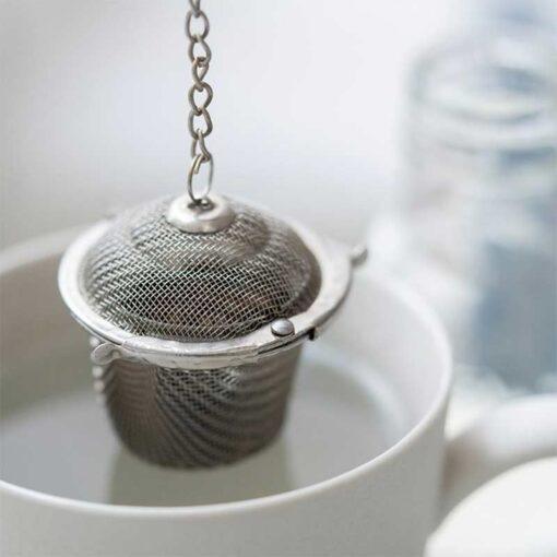 loose tea basket hanging in mug of water
