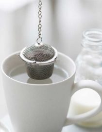 loose tea basket hanging over mug of water