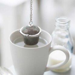 loose tea basket hanging over mug of water