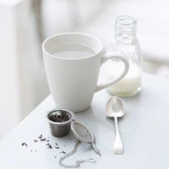 loose tea basket beside mug on table