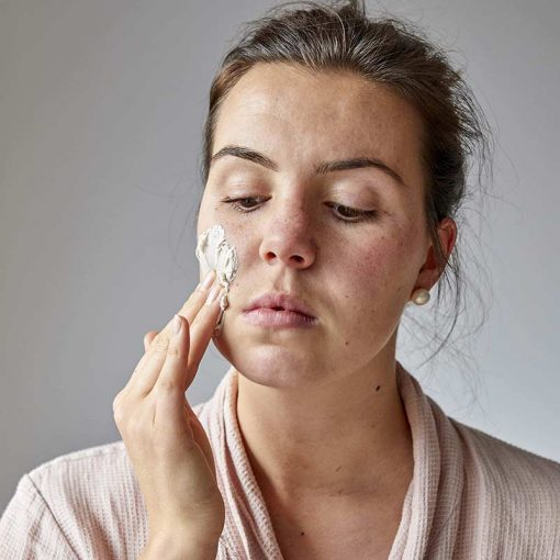 woman applying cleansing face mask
