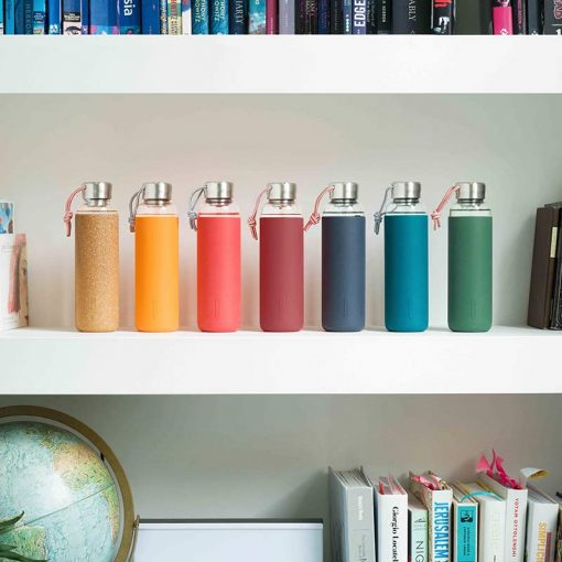 glass water bottles on a shelve with books