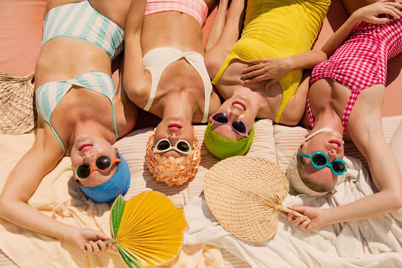 women sunbathing on the beach with mineral sunscreen