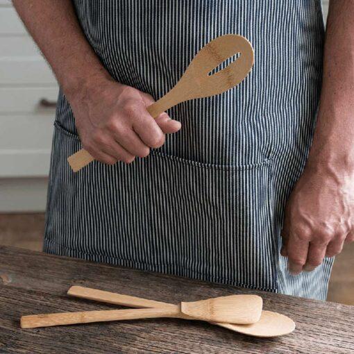 chef holding a bamboo spatula