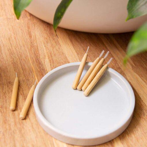 bamboo interdental brushes in white bowl