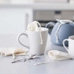 reusable tea bags on a kitchen side next to teapot