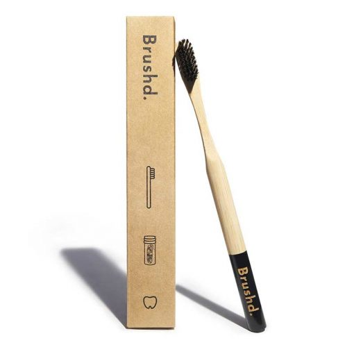 adult bamboo toothbrush next to packaging