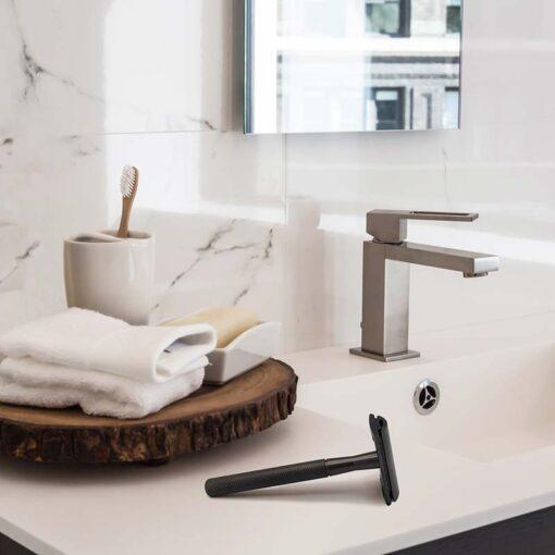 black metal safety razor next to sink