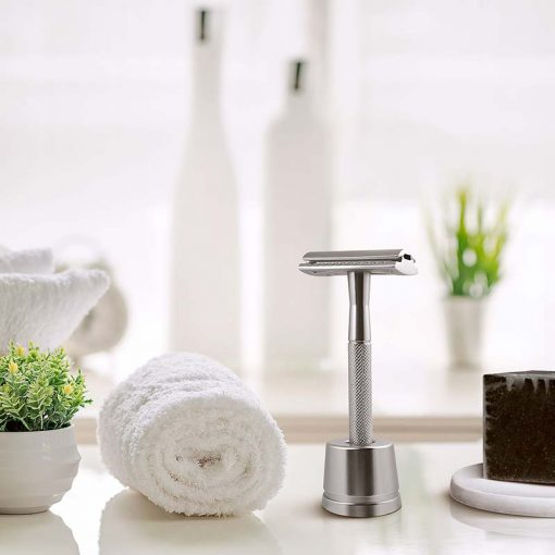 silver safety razor next to a towel