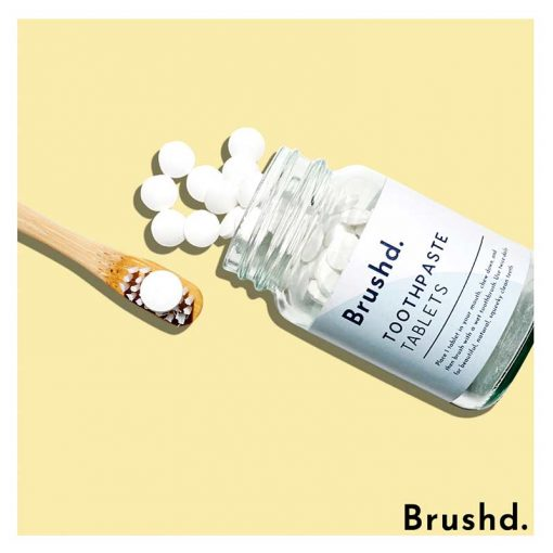 fluoride tothpaste tablets next to bamboo toothbrush