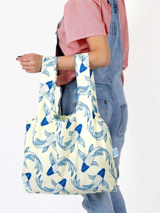 woman holding koi fish shopping bag