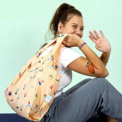 girl holding reusable shopping bag