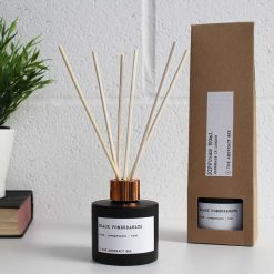 black pomegranate reed diffuser next to packaging