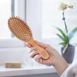 woman holding a bamboo hairbrush