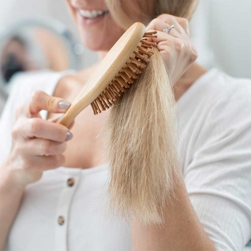 woman using a bamboo hairbrush
