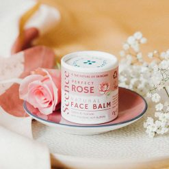 rose face balm next to flowers