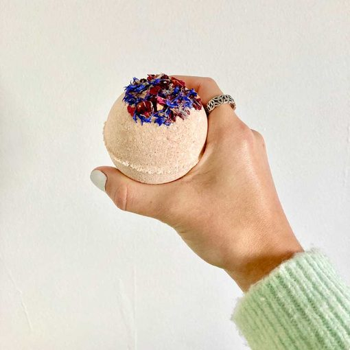 juicy lucy clay bath bomb in a womans hand