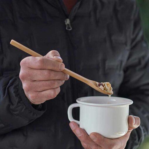 man using a long handle bamboo spoon