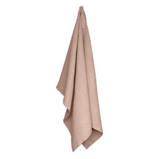 pink waffle bath towel hanging up