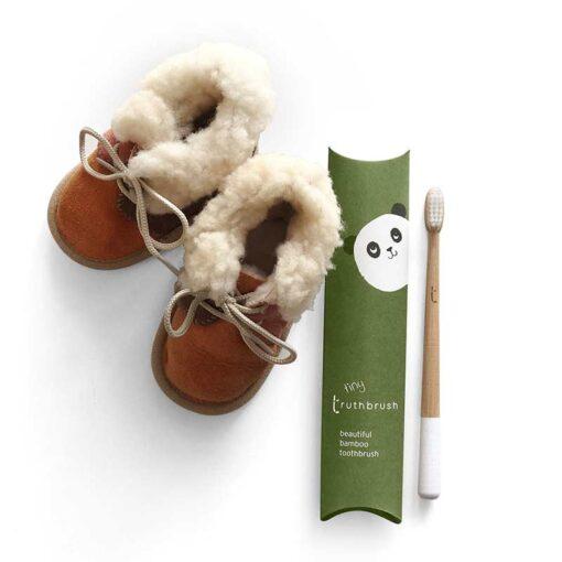 childrens bamboo toothbrush next to kids slippers