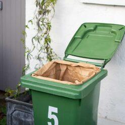 green wheelie bin with wheelie bin liner inside