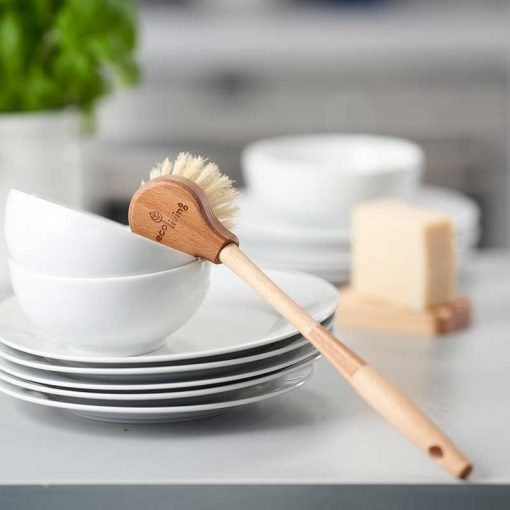 extra long wooden dish brush leaning on washed plates