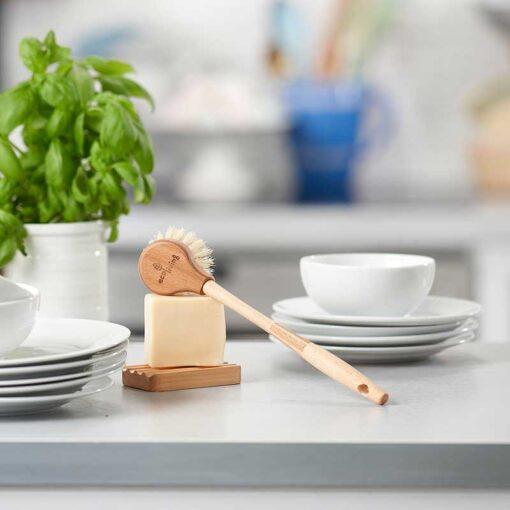 extra long wooden dish brush leaning on dish washing soap bar