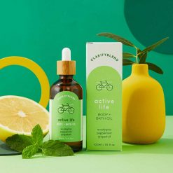 active life body and bath oil on green background