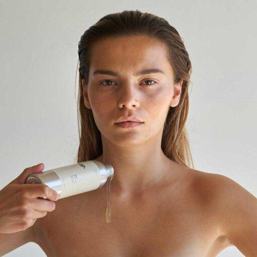 woman with a sop bodywash bottle