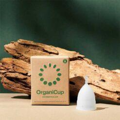 organicup menstrual cup next to a log