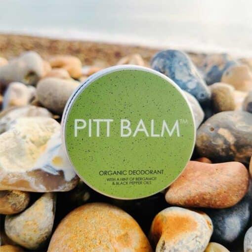 pitt balm natural deodorant on a stony beach