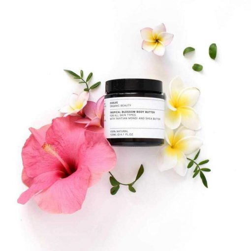 Evolve Tropical Blossom Organic Body Butter next to flowers